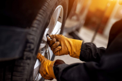 An experienced mechanic with orange gloves is putting screws on a placed wheel on a car.